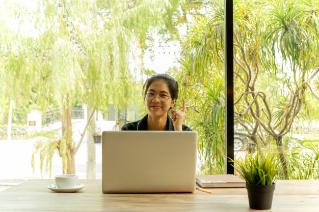 asian-woman-puts-finger-up-thinking-idea-with-laptop-coffee-shop_42667-657