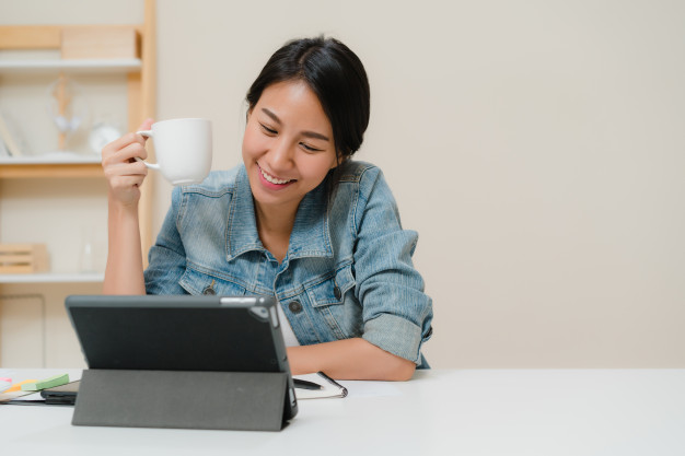 young-asian-woman-working-using-tablet-checking-social-media-drinking-coffee-while-relax-desk-living-room-home_7861-1385